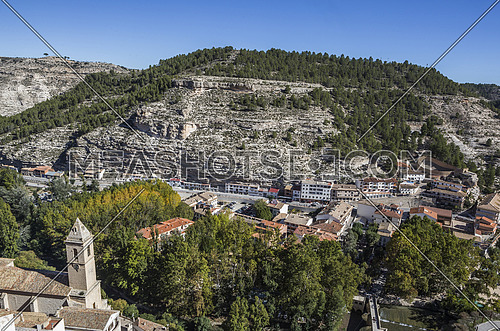 Alcala del Jucar, Spain - October 29, 2016: To the left the church of San Andres and to the right the roman bridge, panoramic view from the castle during autumn, take in Alcala of the Jucar, Albacete province, Spain