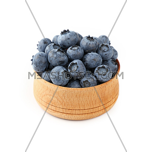 Portion of fresh blueberry berries in rustic wooden bowl isolated on white background, close up, high angle view