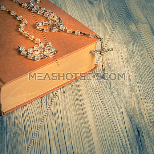 vintage rosary beads on old books, square photo.