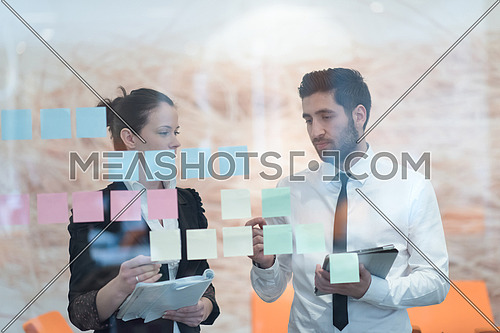 young creative startup business people on meeting at modern office making plans and projects with post stickers on glass