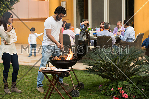 happy middle east family enjoying the beautiful summer afternoon with a barbecue in the garden