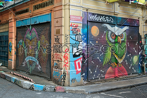 Istanbul, Turkey - April 18, 2017:  Closed shop exteriors with metal rolling doors painted with colorful graffiti at Hoca Tahsin Street, Karakoy district, Istanbul, Turkey