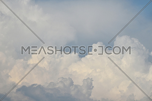 Beautiful cloudscape with heavy massive white clouds over blue sky, low angle view