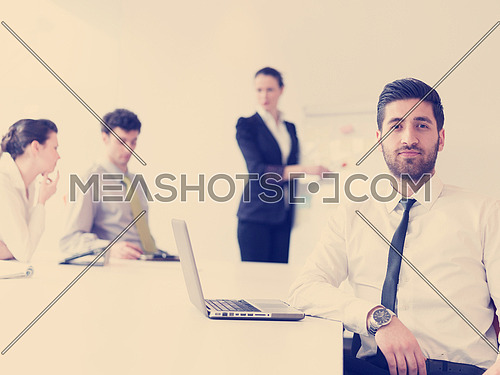 portrait of young modern arab business man with beard at office,   group of  business people  on meeting making presentation  in background