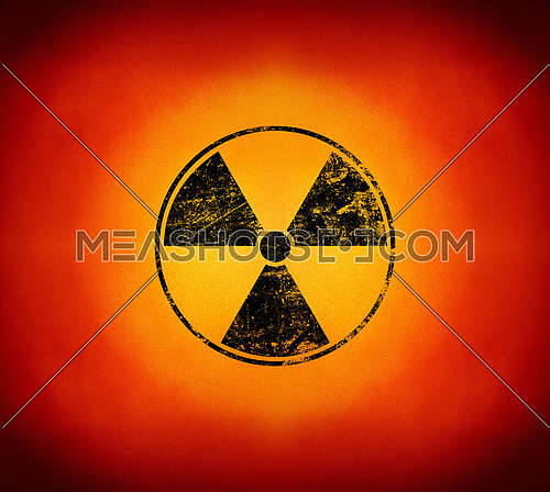 Black radioactive hazard warning sign painted over grunge yellow and red background with copy space