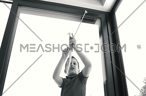 Boy palying with bow toy in bright home