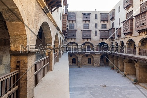 Facade of Caravanserai of Bazaraa, with vaulted arcades, windows, and arab oriel windows - mashrabiya - suited in Tombakshia street, Al Gamalia district, Medieval Cairo, Egypt