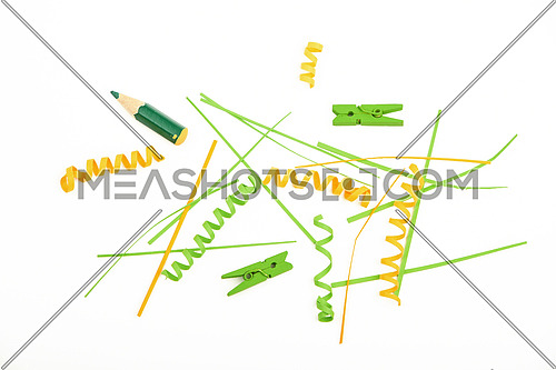 Mixed colorful green and yellow paper pieces, clips, pencils and wooden painted clothespins isolated on white background