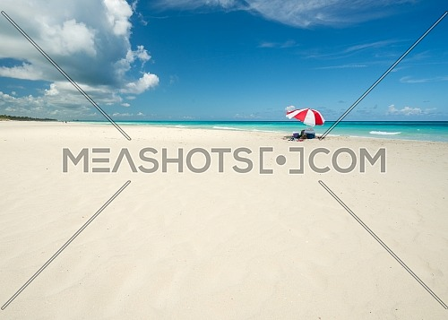 Wonderful beach of Varadero during a sunny day, fine white sand and turquoise and green Caribbean sea,on the right one red parasol,Cuba.concept photo,copy space.