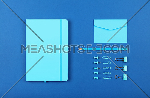 Neatly organized stationery flat lay of pastel blue notebook, envelope, pencil, office clips, binders and pins in order over dark indigo blue background, elevated top view, directly above