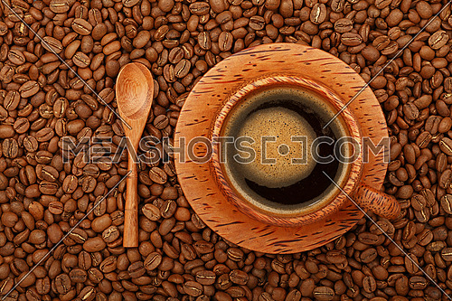 Brown coconut palm carved wood cup full of black coffee with froth on wooden saucer and spoon over background of roasted coffee beans, elevated top view, directly above