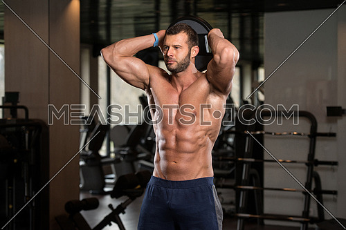 Young Man Exercising Abs With Weights In A Modern Fitness Gym