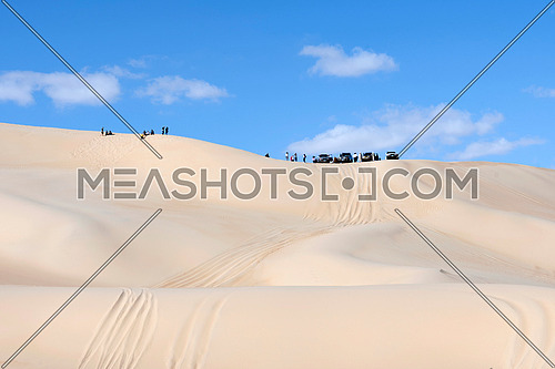 Group of tourists with 4wheel drive safari cars on top of high sand dunes in Siwa Oasis Desert , Egypt Adventure and Nature Tourism