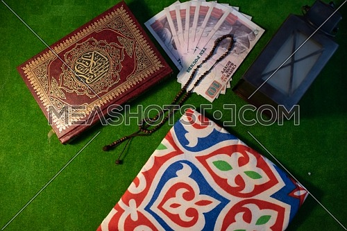 Top shot for Holly Quran Book closed with Misbaha beside showing Ramadan Lantern and money.