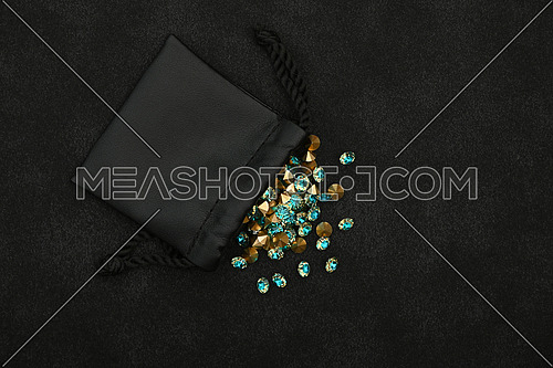 Close up heap of teal blue rhinestone crystals spilling out of leather bag over black background, elevated top view, directly above
