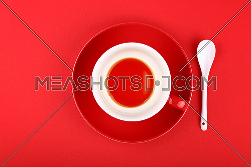 Empty cup of black tea on porcelain saucer with white ceramic spoon over vivid red paper background, close up, elevated top view, directly above
