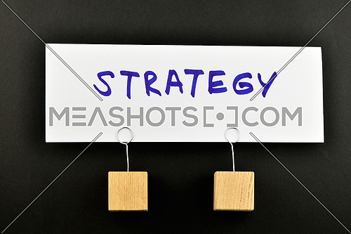Strategy, One big white paper note with two wooden holders isolated on black paper background for presentation