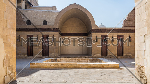Courtyard of public historic mosque of Sultan Al Nassir Qalawun with side arched iwan and closed wooden doors, Cairo, Egypt