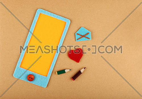 Close up felt craft blue smartphone with yellow blank screen copy space, heart and mail envelope over brown paper background, elevated top view, directly above