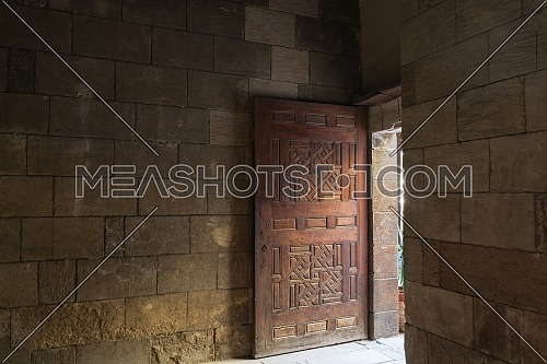 Old abandoned room with stone bricks and grunge weathered wooden decorated door, Old Cairo, Egypt