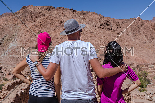Group of tourists from behind exploring Sinai Mountain for wadi Freij by day.