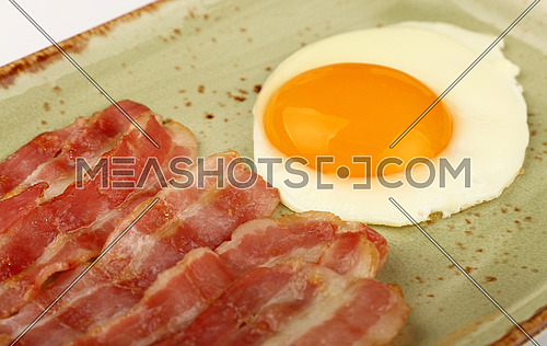 Close up English breakfast, sunny side egg and roasted bacon slices on blue plate, high angle view