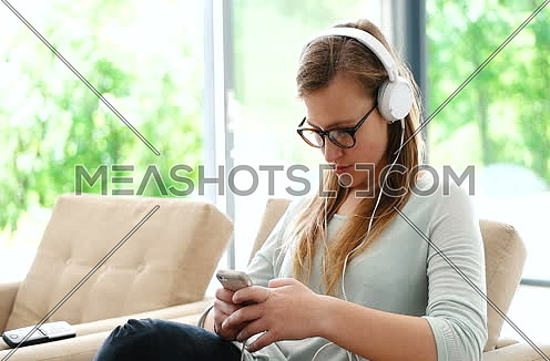 woman listening to music on cellphone at villa