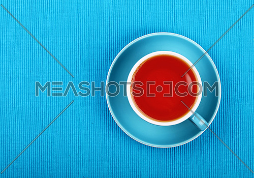 Full cup of black tea on saucer over blue tablecloth, close up, elevated top view