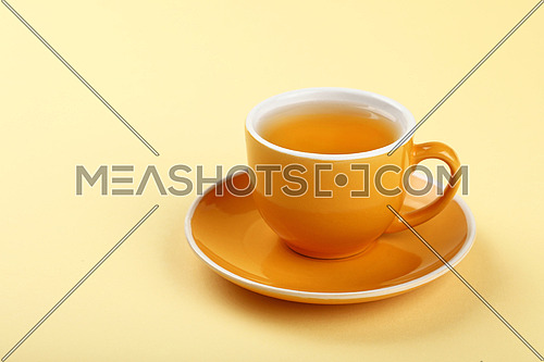 Close up one full yellow cup of green oolong or herbal tea on saucer over pastel paper background, high angle view
