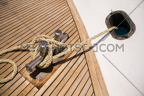 Boat deck wooden floor showing an anchor rope tied to the boat