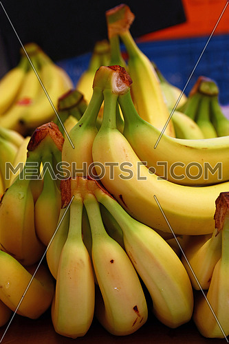 Heap of fresh yellow ripe bananas on retail market stall display, close up, low angle view