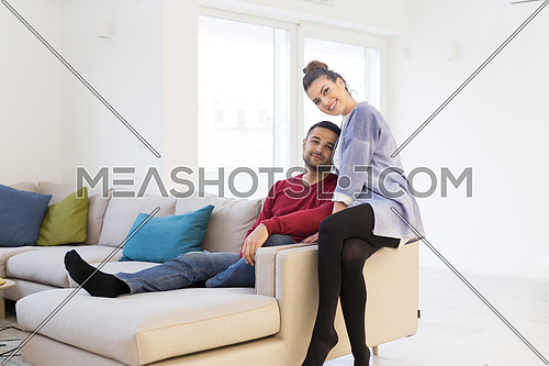 Happy young couple hugging and relaxing on sofa at home