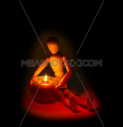 wood mannequin and candle glowing on the dark over black background