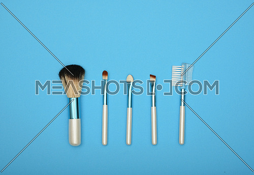 Close up set of different natural face makeup brushes over blue background, elevated top view, directly above