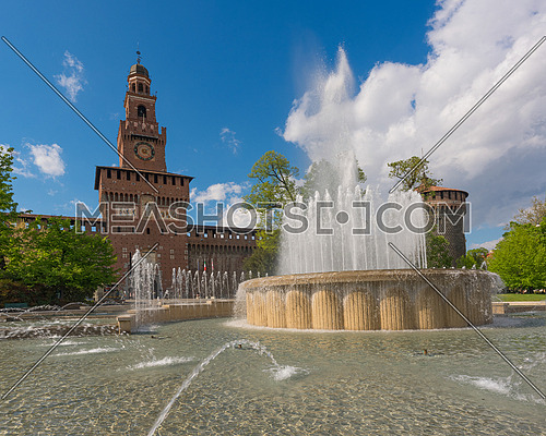 Main entrance to the Sforza Castle - Castello Sforzesco and fountain in front of it, sunny day and clouds in the sky,Milan, Italy