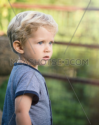 wonderful baby boy,blue eyes and blond hair looks towards the emptiness in the garden, natural light.