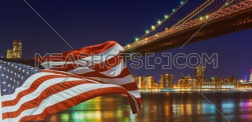 Brooklyn Bridge closeup over East River at night in New York City Manhattan and American flag flying, USA