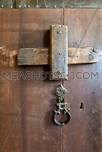 Front view closeup of a wooden aged latch, rusted ring door knob, and keyhole over a wooden opened door