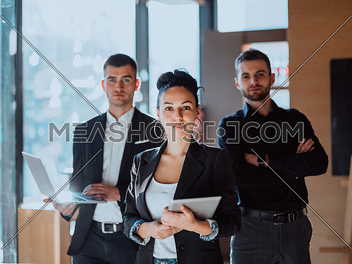 Business concept .A portrait of a group of entrepreneurs in a modern office holding modern work equipment.