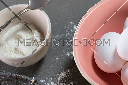 eggs in pink and yellow bowl and flour in beige bowl