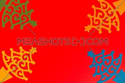 Merry Christmas red background decorated with paper cut Christmas trees. Winter holiday card decorations concept, flat lay with free copy space
