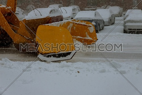 Clearing by the excavator of snow on the streets