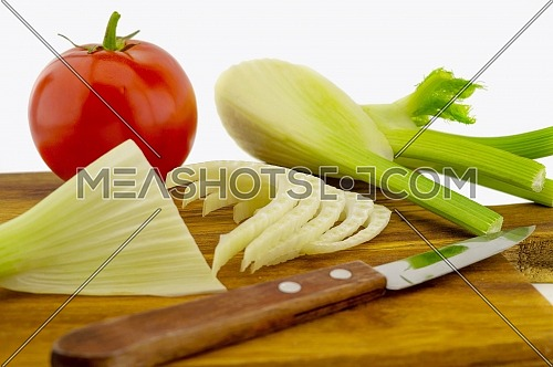 Preparing red tomato and fresh fennel slicing them on a wooden cutting board over a white background in a healthy diet and nutrition concept