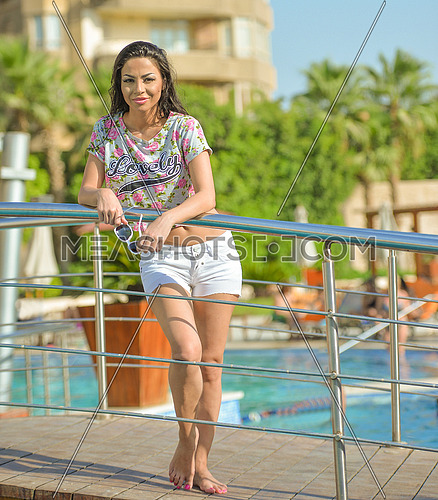 Lebanese singer and actress Dolly Shahin by the pool summer 2017 wearing white shorts and colorful showing stomach blouse.