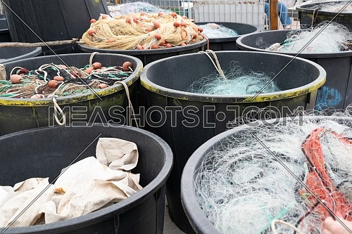 Fishing nets inside huge plastic bins on the waterfront after fishing day,quayside of the port of Varazze, Liguria Italy.