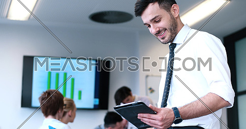 Businessman using tablet computer in office with coworkers in background