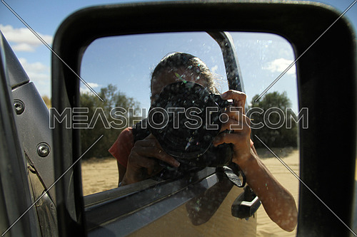 Cute young middle eastern female photographer with camera. Woman reflected in the rearview mirror of a car on a summer day