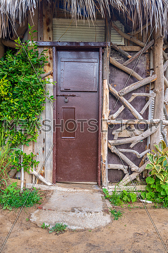 Closed wooden brown grunge door and thatch roof, surrounded by green bushes at Montaza public park, Alexandria, Egypt