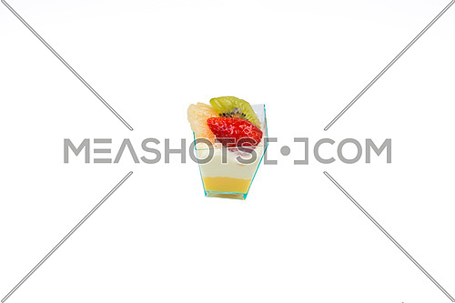In the picture a cupcake with fruit,cream and custard in a plastic cup,isolated on white background.