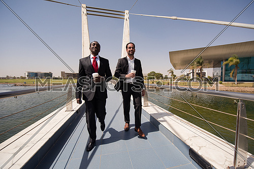 multi ethnic business people group walking across modern bridge while drinking first morning coffee